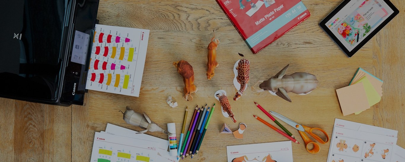 A Canon printer surrounded by templates for paper animals, coloured pencils, glue and a pair of scissors.